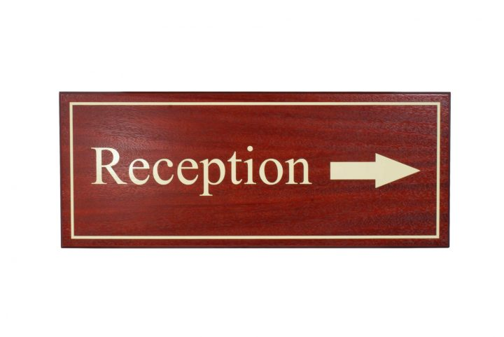 custom made hotel reception sign in wood and mahogany stain and lacquer